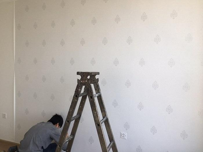 Bóc keo và dán vào tường sau khi đo đạc thực tế diện tích